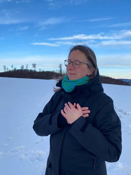 Ayurveda hat mir so geholfen. Ich stehe mit geschlossenen Augen und den Händen vor dem Herz verschränkt auf einer schneebedeckten Wiese.